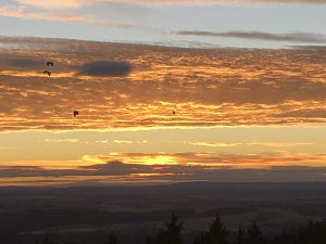 Gleitschirmflieger über Beggingen vor der untergehenden Sonne.