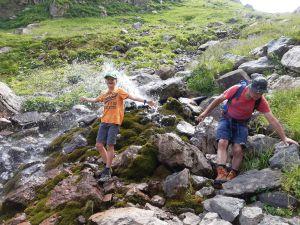 Spriztende Quelle, oberhalb Seealpsee im Alpstein bei Wasserauen. Sohn Manuel und sein Vater Päuli erfreuen sich ab der spontanen Erfrischung während der Wanderung.