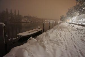 """Das Foto wurde am 15.1.21 morgens um 6.30 Uhr aufgenommen. Es war noch dunkel. Man sieht den vorderen Teil vom Lindli. Ich war auf dem Weg ins Geschäft. An diesem Tag bin ich früher als üblich los.  Ich wollte diese besondere, verschneite Stimmung festhalten. Ich liebe den Rhein im Sommer. Aber auch im Winter hat es etwas Mystisches. Wann gab es je so viel Schnee bei uns im Unterland? Das ist für mich """"ein ganz besonderer Winter"""". Doch ich war spät, denn es hatte bereits Fussspuren im Schnee ;-)"""